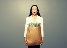 Amazed woman holding paper bag with money. Amazed businesswoman holding paper bag with money and looking at camera. photo in studio over grey background Royalty Free Stock Image