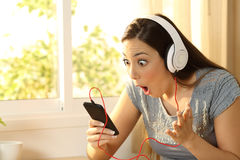 Amazed woman listening music finding offer. S on line in a smart phone in her room Stock Photo