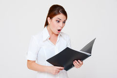 Amazed woman looking in her report. Over grey background Royalty Free Stock Photos