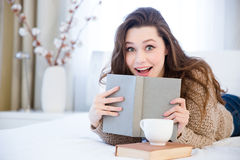 Amazed woman lying on bed and reading book in bedroom. Happy amazed charming young woman lying on bed and reading book in bedroom Stock Image