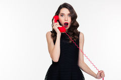 Amazed woman with makeup in retro style talking on  telephone. Amazed beautiful curly woman with bright makeup in retro style talking on red telephone isolated Royalty Free Stock Photography