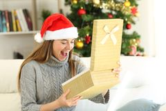 Amazed woman opening a gift box on christmas stock photo