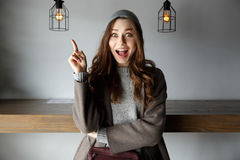Amazed woman pointing up and having idea in cafe Royalty Free Stock Photo