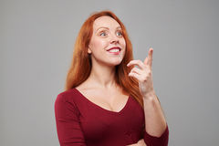 Amazed woman pointing upwards. Close-up of amazed woman pointing upwards to a copy space. Woman in vinous dress looking and pointing Royalty Free Stock Photo