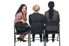 Amazed woman at presentation. Rear view of three business woman in a row watching  a presentation and one of them returns her head with amazed face isolated on Royalty Free Stock Images