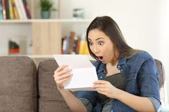 Amazed woman reading surprising news in a letter stock photography