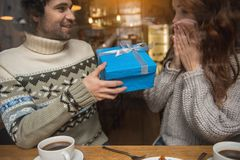 Amazed woman receiving present from her lover. Congratulations. Excited girl is looking at gift box in male arms with amazement. Man is sitting at table and Stock Photography
