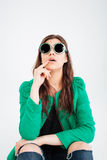 Amazed woman in round sunglasses sitting and looking up Royalty Free Stock Image