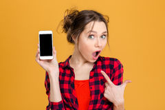 Amazed woman showing blank smartphone screen. Portrait of a young amazed woman showing blank smartphone screen over yellow background. Focus on smartphone Stock Images