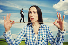 Amazed woman and small man on the rope Stock Images