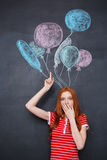 Amazed woman standing over blackboard background with drawn balloons Royalty Free Stock Images