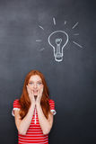 Amazed woman standing over chalkboard background with drawn electric bulb Royalty Free Stock Photos