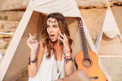 Amazed woman talking on cell phone in teepee at beach. Pretty amazed young woman talking on cell phone in teepee on the beach Royalty Free Stock Photos
