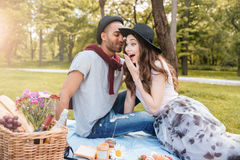 Amazed woman talking and having picnic with her boyfriend. Amazed attractive young women talking and having picnic with her boyfriend in park Royalty Free Stock Photos