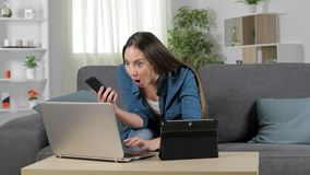 Amazed woman using multiple devices. Sitting on a couch at home stock video