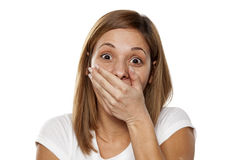 Amazed woman. Amazed young woman covering her mouth with her hand on white background Stock Images
