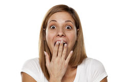 Amazed woman. Amazed young woman covering her mouth with her hand on white background Royalty Free Stock Photography