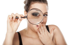 Amazed woman. Amazed young woman looking through a magnifying glass Royalty Free Stock Photos