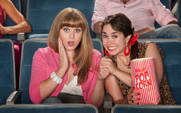 Amazed Women In Theater. Two amazed women with bag of popcorn watch movie in theater Royalty Free Stock Images