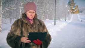 Amazed wow woman looking a tablet application in a snowy mountain on vacations. Amazed wow woman looking a tablet application in a snowy mountain vacations stock footage