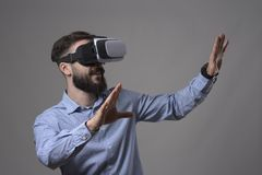 Amazed young adult bearded smart casual man wearing virtual reality vr headset gesturing hands and looking at copyspace Stock Images