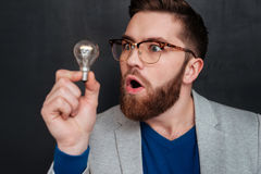 Amazed young bearded man in eyeglasses looking at light bulb. Confused amazed young bearded man in eyeglasses looking at light bulb over black backgorund Royalty Free Stock Photography