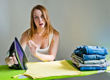 Amazed young beautiful woman ironing clothes. Royalty Free Stock Photography