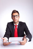 Amazed young business man with pad. Amazed young business man looking at something imaginary above his pad , sitting at his desk Royalty Free Stock Photos