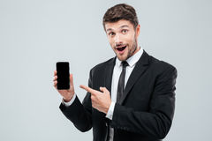 Amazed young businessman holding and pointing on blank screen smartphone. Over white background Stock Image