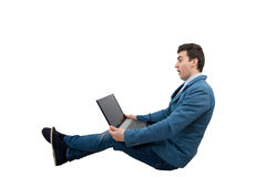 Amazed young businessman. Looking at a laptop monitor while sitting down Royalty Free Stock Photos