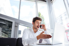 Amazed young businessman using laptop and talking on mobile phone. In office Stock Images