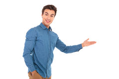 Amazed young casual man presenting. Something on white background Royalty Free Stock Photo