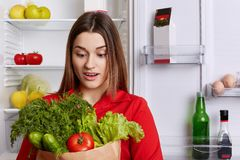 Amazed young female with surprised expression looks at vegetables, forgets to buy something in grocer`s shop, stands in kitchen ne. Ar refrigerator. People Stock Photo