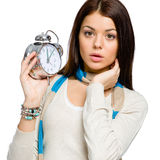 Amazed young girl with alarm clock. Wearing colored scarf and beige pullover, isolated on white Stock Photo