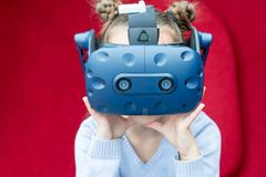 Amazed young girl experiencing virtual reality with a VR headset on the head. royalty free stock images