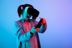 Amazed young girl playing a game. With virtual reality headset on blue background Stock Image