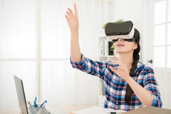 Amazed young girl testing virtual reality 3D video. Glasses VR headset in a office by reality sitting in the studio with curious hands gesticulating moving in Stock Image