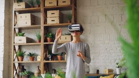 Amazed young lady is enjoying new experience in augmented reality glasses standing in flat and moving hands reaching in. Syberspace. Technology, millennials and stock video