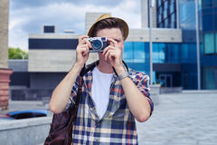 Amazed young man with camera takes photos in downtown Royalty Free Stock Image