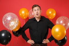 Amazed young man in classic shirt looking aside, standing with arms akimbo on red background air balloons. Valentine`s. International Women`s Day, Happy New royalty free stock image