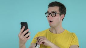 Amazed Young Man Excited while Using Smartphone Isolated on Blue Background. The Amazed Young Man Excited while Using Smartphone Isolated on Blue Background stock video