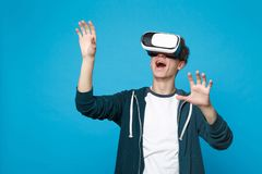 Amazed young man in headset touch something like push click on button, pointing at floating virtual screen isolated on. Blue background. People sincere emotions stock photography
