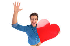 Amazed young man holding a red heart. With hand in the air isolated on white background Royalty Free Stock Image