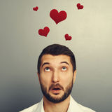 Amazed young man looking up. Concept photo of man in love. amazed young man looking up at red hearts over grey background Royalty Free Stock Photo