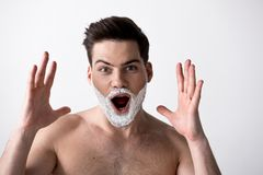 Amazed young man is posing with foam on cheeks stock images
