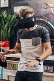 Amazed young man wearing virtual reality goggles playing an interactive game trying to touch something at home.  Stock Photos