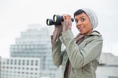 Amazed young model in winter clothes holding binoculars Royalty Free Stock Photo