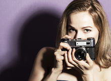Amazed young pretty woman holding camera and looking ahead. Amazed young pretty woman holding camera and looking at camera Royalty Free Stock Photo