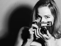 Amazed young pretty woman holding camera and looking ahead. Amazed young pretty woman holding camera and looking at camera Stock Photography
