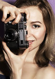 Amazed young pretty woman holding camera and looking ahead. Amazed young pretty woman holding camera and looking at camera Stock Image